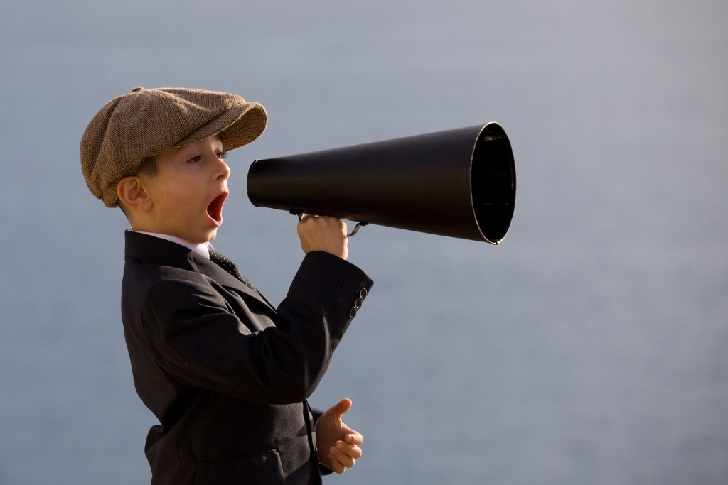 little-boy-wearing-flat-cap-shouting-on-old-fashioned-megaphone-picture-id154926743